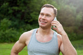 Man stands with a telephone in the park — Stock Photo