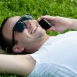 Smiling young guy speaking on mobile phone — Stock Photo #27652947