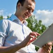 Businessman at the park with tablet — Stock Photo