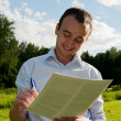 Business man working with papers at park — Stock Photo