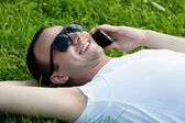 Smiling young guy speaking on mobile phone — Stock Photo