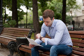 Man reading documents in the public garden — Stockfoto