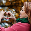 Beautiful woman in pink coat showing heart in the Park — Stock Photo