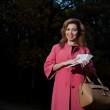Beautiful woman in pink coat with book walks in the Park — Stock Photo