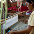 A weaver adjusts the silk cloth on her loom — Stock Photo