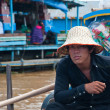 Asian boy sitting in the boat and selling some souvenirs — Stock Photo