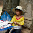 Little asian boy sitting with some souvenirs for sale — Stok fotoğraf