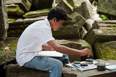 Asian boy paint a picture for sale — Stock Photo