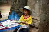 Little asian boy sitting with some souvenirs for sale — Stock Photo
