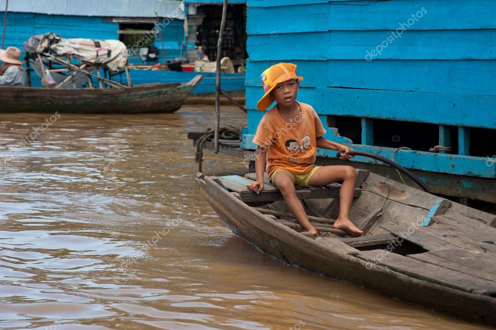 River+Boat+Plans Asian boy sitting in the boat on the river near his ...