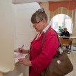 Woman fills election ballot with candidates for mayor — Stock Photo #36338697
