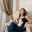Young pregnant woman sits on chair — Foto Stock