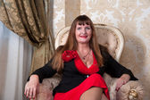 Senior woman sits on chair — Stock Photo