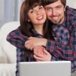 Young laughing couple using laptop while sitting on couch — Stock Photo