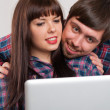 Portrait of young smiling couple using laptop at home — Stock Photo