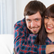 Portrait of young love couple sitting on couch and smiling — Stock Photo