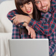 Couple using laptop while sitting on couch at home. Man embrace — Stock Photo