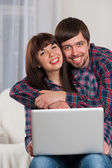 Young laughing couple using laptop while sitting on couch at hom — Stock Photo