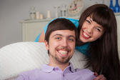 Young woman stand behind her boyfriend sitting on the couch — Stock Photo