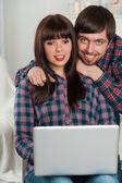 Mladý pár použití notebooku doma — Stock fotografie