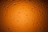 Water drops on glass with orange background — Stockfoto