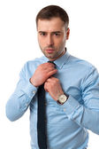 Business man corrects tie — Stock Photo