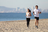 Man and woman running in the beach — Stock Photo