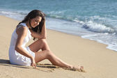 Beautiful woman drawing a heart in the sand — Stock Photo