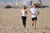 Man and woman running on the beach — Stock Photo