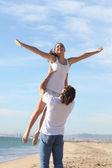 Homem na praia levantando sua namorada — Foto Stock