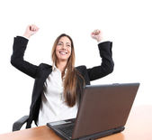Euphoric businesswoman in an office with a laptop — Stock Photo