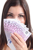 Beautiful woman smiling and holding a lot of five hundred euro banknotes — Stock Photo