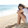 Portrait of a worried girl sitting on the beach — Stock Photo
