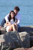 Zärtlich paar flirten und umarmt auf einem stein am strand — Stockfoto