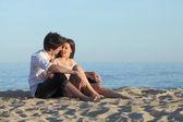 Para flirty siedzi na piaszczystej plaży — Zdjęcie stockowe