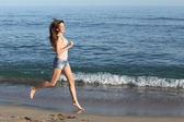 Beautiful casual woman running on the beach — Photo