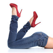 Close up of a beautiful woman legs with blue jeans and red heels — Stock Photo