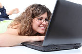 Beautiful woman lying and browsing in a laptop — Stock Photo