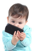 Casual baby watching attentive a mobile phone — Stock Photo