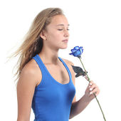 Beautiful woman holding and smelling a blue rose — Stock Photo