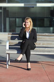 Businesswoman on the mobile phone sitting on a bench — Stock Photo