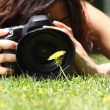Close up of a pretty girl taking a photograph of a flower on the grass — Stock Photo
