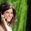 Stock Photo: Attractive womsmiling on phone in park