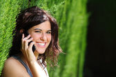 Attractive woman smiling on the phone in a park — Stock Photo