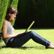 Attractive womhappy in park with laptop — Stock Photo #26659919