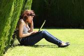 çekici bir kadın çim bir parkta otururken bir laptop ile sıkılmış — Stok fotoğraf