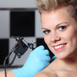 Stock Photo: Hands making tattoo on womshoulder