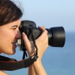 Attractive woman taking a photograph with her camera — Stock Photo