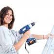 Beautiful woman with a drill on a ladder — Stock Photo