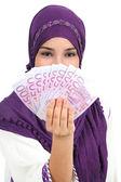 Beautiful islamic woman wearing a hijab showing a lot of banknotes — Stock Photo